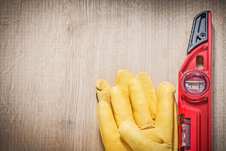 construction level: Leather protective gloves red construction level on wooden board. Stock Photo
