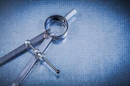 compas de dibujo: Metal construction drawing compass on metallic background.