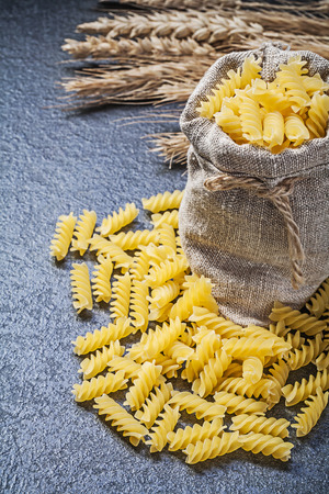 shortcut: Sack short-cut uncooked macaroni golden wheat rye ears on black background.