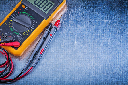 dielectric: Digital electric tester on metallic background. Stock Photo