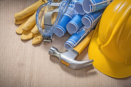protective workwear: Protective workwear rolled blueprints claw hammer on wooden board construction concept. Stock Photo