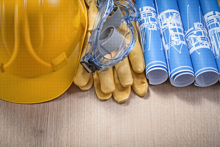 protective gloves: Hard hat protective gloves glasses blue engineering drawings on wood board construction concept.