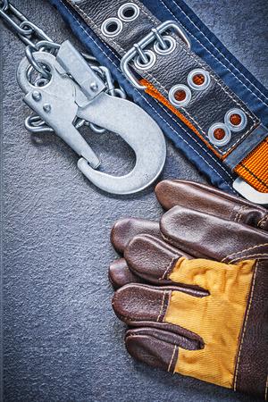 cinturon seguridad: seguridad en la construcci�n de la correa de cuero de los guantes sobre fondo negro concepto de mantenimiento.