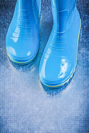 gumboots: Pair of waterproof gumboots on metallic background.