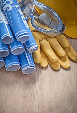 protective workwear: Protective workwear blue rolled engineering drawings on wooden board construction concept.