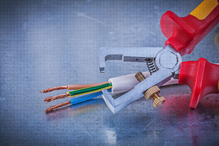 cable cutter: Insulation strippers electric wires on metallic background horizontal view electricity concept.
