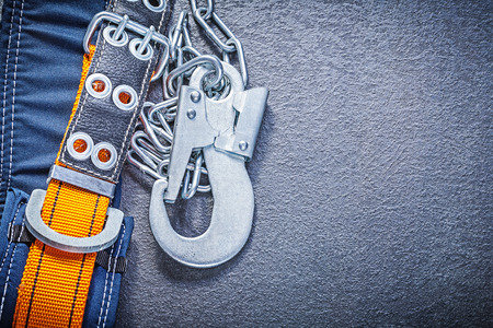 safety harness: Safety harness with metal chain carabiners on black background construction concept.