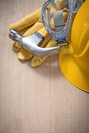 protective workwear: Protective workwear claw hammer on wooden board construction concept vertical version.