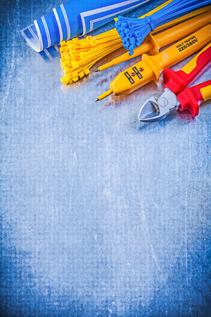 cable tie: Yellow electrical tester self-locking tying cables blue blueprints nippers on metallic background electricity concept. Stock Photo
