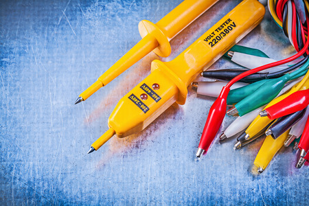 dielectric: Yellow electrical tester set of multicolored crocodile clip cables on metallic background electricity concept.