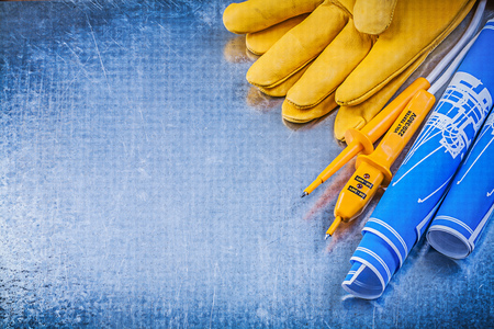 dielectric: Yellow electrical tester protective gloves blue construction plans on metallic background.