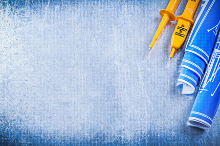 electricity background: Yellow electrical tester blue rolled blueprints on metallic background electricity concept. Stock Photo