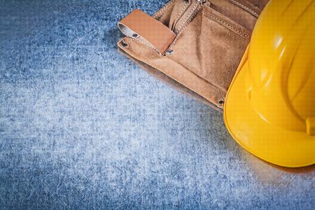 tool belt: Tool belt safety hard hat on metallic background construction concept.