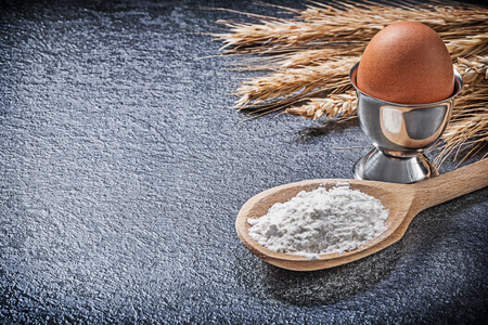 eggcup: Wheat rye ears wooden spoon flour eggcup boiled egg on black background. Stock Photo