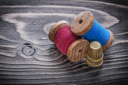 fancywork: Vintage spools of thread thimbles on wooden board fancy-work concept.