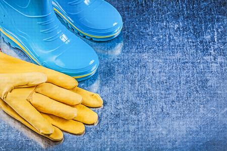 gumboots: Waterproof gumboots leather gloves on metallic background gardening concept.