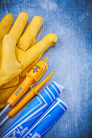 protective gloves: Yellow electrical tester protective gloves blue blueprints on metallic background.