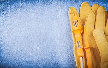 the tester: Yellow electrical tester protective gloves on metallic background copy space. Stock Photo