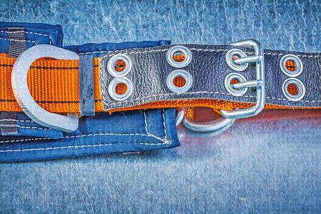 cinturon seguridad: cuerpo de la correa de seguridad de construcción en el fondo metálico rayado.