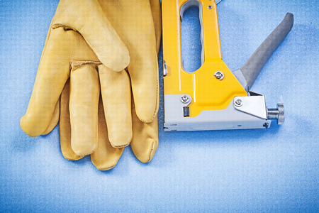 staple gun: Leather working gloves yellow construction staple on blue background top view.