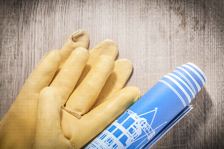 protective: Leather protective gloves rolled blue construction plans on wooden board.