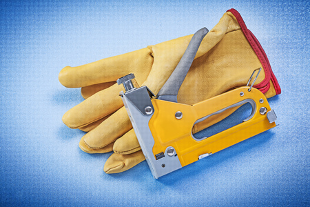 safety gloves: Leather safety gloves stapler gun on blue background construction concept.