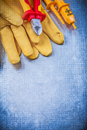 nippers: Yellow electrical tester safety gloves sharp nippers on metallic background electricity concept. Stock Photo