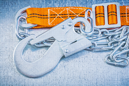 strap: Protective construction strap on scratched metallic background.