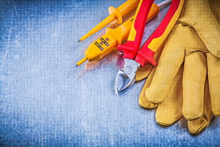 wire cutter: Yellow electrical tester safety gloves red wire cutter on metallic background electricity concept.