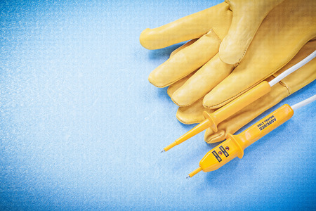the tester: Safety gloves electric tester on blue background electricity concept.