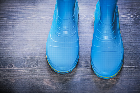 gum boots: Waterproof gardening rubber boots on wooden board agriculture concept.