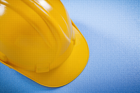 yellow hard hat: Yellow hard hat on blue surface construction concept.