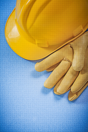 protective gloves: Yellow hard hat leather protective gloves on blue background construction concept. Stock Photo