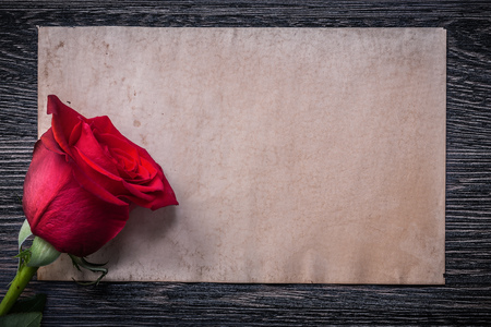 expanded: Vintage paper red natural scented rosebud on wood board.
