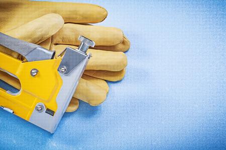 staple gun: Leather safety gloves yellow construction stapler on blue background.