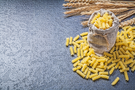 bagging: Bagging sack short-cut spiral pasta golden wheat rye ears on black background.