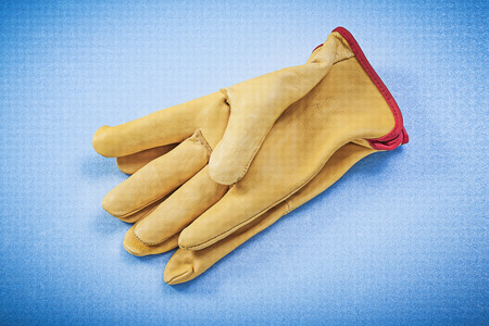 protective gloves: Pair of leather yellow protective gloves on blue background construction concept.
