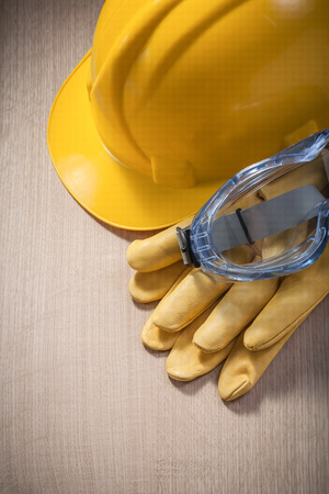 protective spectacles: Set of hard hat protective gloves spectacles on wooden board construction concept.