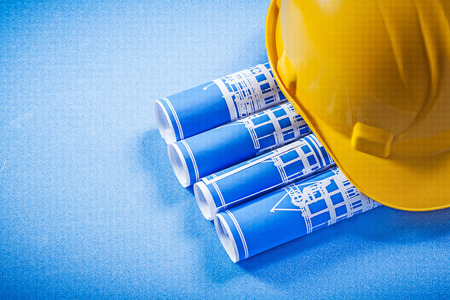 hard hat: Rolled up construction plans hard hat on blue background.