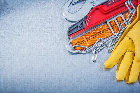 cinturon seguridad: nivel de guantes de protección de construcción del cinturón de seguridad en el fondo metálico. Foto de archivo
