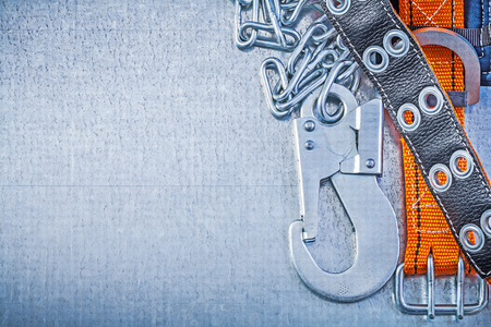 safety belt: Safety belt metal chain carabiner hook on metallic background copy space.