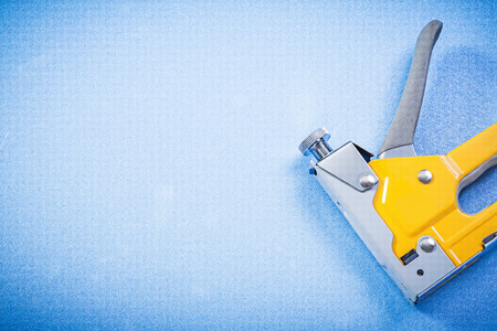 staple gun: Metal staple gun on blue background construction concept. Stock Photo