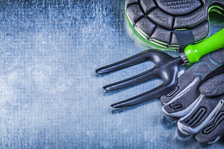 protectors: Gardening protective gloves knee protectors trowel fork on metallic background agriculture concept.