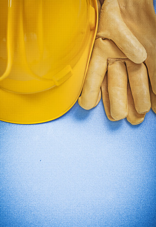 yellow hard hat: Composition of yellow hard hat protective gloves on blue background construction concept.