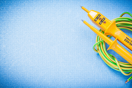 the tester: Yellow electrical tester cable on blue background electricity concept.
