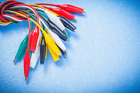 dielectric: Assortment of electric crocodile clip cables on blue background electricity concept.