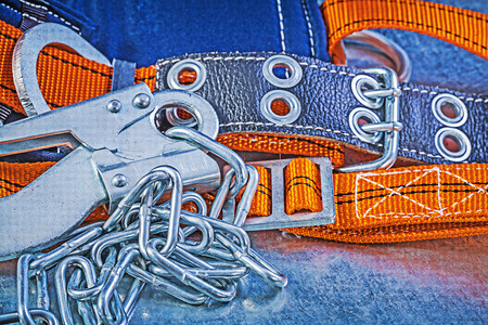 metal chain: Construction harness metal chain carabiner hook on metallic background top view.