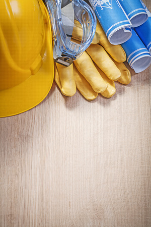 protective spectacles: Hard hat protective gloves glasses blue blueprints on wooden board construction concept.