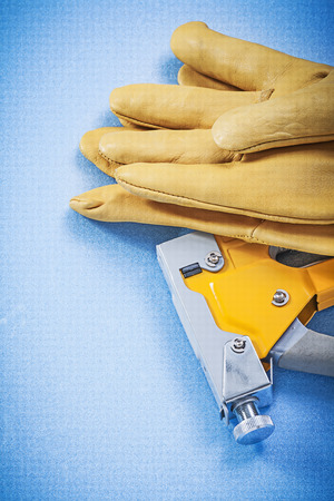 protective gloves: Leather protective gloves yellow construction stapler on blue background vertical view.
