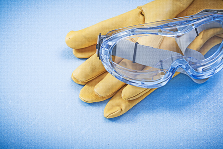protective spectacles: Leather safety gloves goggles on blue background construction concept. Stock Photo